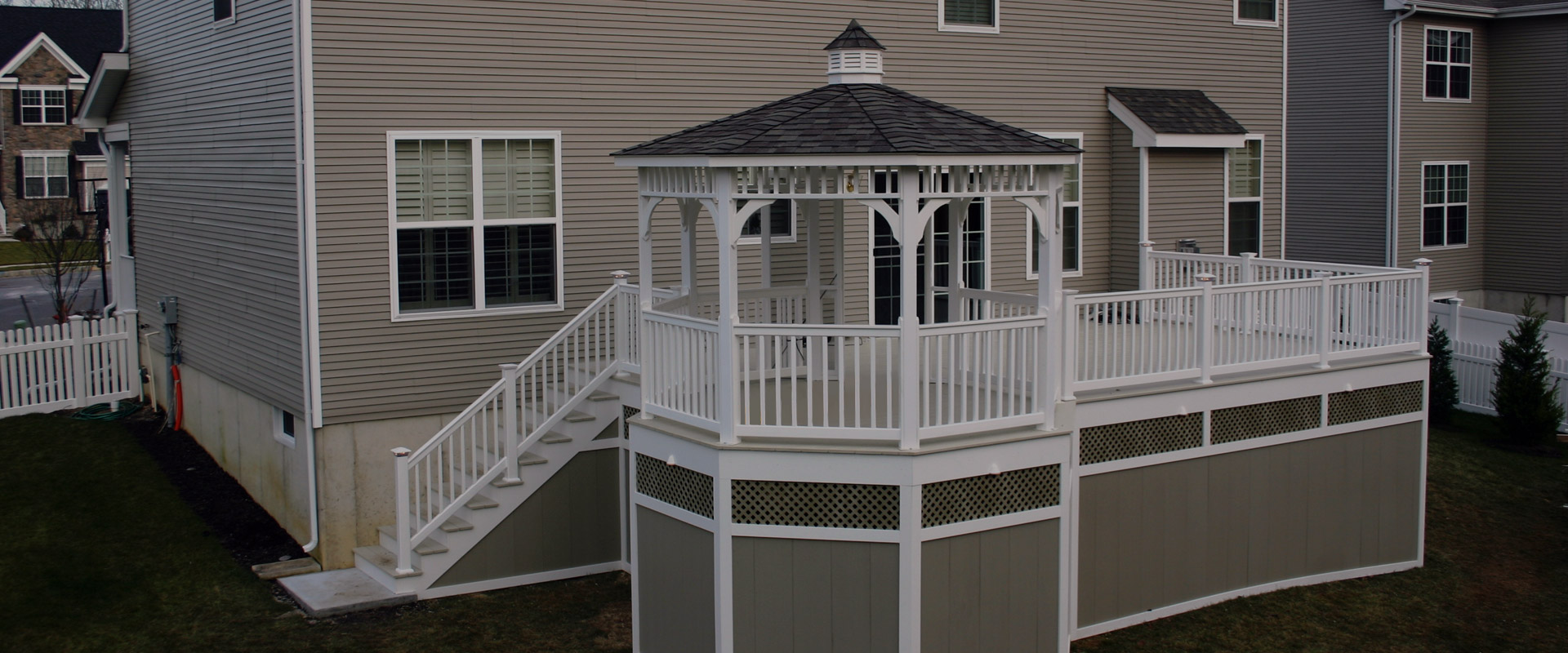white deck gazebo on tan house